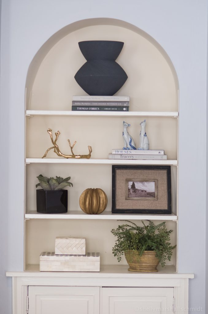 Image of a styled bookshelf. The Art of Accessorizing